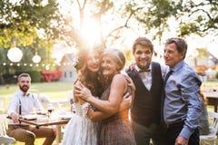 Novia, novio con los padres que presentan para la foto en la recepción nupcial afuera en el patio trasero fotografía de archivo libre de regalías