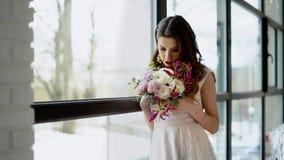 Novia preciosa con el ramo de flores dentro almacen de metraje de vídeo