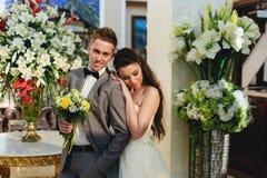 Novia que abraza al novio en el fondo de flores Imagenes de archivo