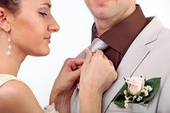 Novia que ajusta el lazo del novio Imagenes de archivo