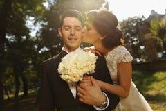Novia que besa a su novio Fotografía de archivo