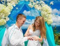 Novia que da un anillo de compromiso a su novio debajo del deco del arco fotos de archivo