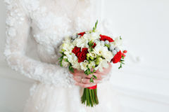 Novia que detiene cierre nupcial del ramo rosas rojas y blancas, fresia, brunia adornadas en la composición Fotos de archivo