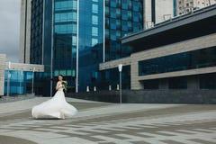 Novia que gira delante del alto edificio Imagenes de archivo