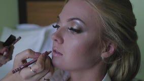 Novia que hace maquillaje antes de la boda Una mujer joven toma a un estilista metrajes