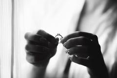 Novia que lleva a cabo el anillo en manos cerca de la ventana fotos de archivo