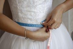Novia que mide su cintura antes del día de boda foto de archivo libre de regalías