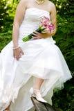 Novia que muestra apagado la alineada y los zapatos de boda foto de archivo
