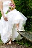 Novia que muestra apagado la alineada y los zapatos de boda fotos de archivo