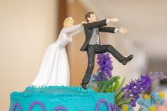 Novia que persigue la torta de Wedding Decoration On del novio fotografía de archivo