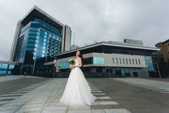 Novia que se coloca delante del alto edificio Imagenes de archivo