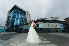 Novia que se coloca delante del alto edificio Foto de archivo