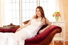 Novia que se relaja en el sofá de desfallecimiento fotografía de archivo