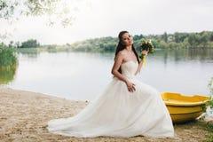 Novia que se sienta en el barco en la orilla del río Fotos de archivo