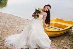 Novia que se sienta en el barco en la orilla del río Fotografía de archivo libre de regalías