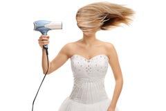 Novia que sopla su pelo con un secador de pelo imagenes de archivo