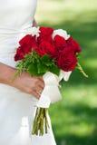 Novia que sostiene el ramo color de rosa del rojo Imagen de archivo libre de regalías