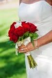 Novia que sostiene el ramo color de rosa del rojo Foto de archivo libre de regalías