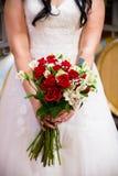 Novia que sostiene el ramo color de rosa del rojo Imagen de archivo