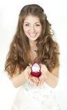 Novia que sostiene el rectángulo rojo con los anillos de bodas de oro. Fotografía de archivo libre de regalías