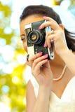 Novia que toma el cuadro con una cámara retra vieja Fotografía de archivo libre de regalías