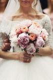 Novia rubia elegante sonriente con el ramo color de rosa de la boda en blanco Foto de archivo libre de regalías