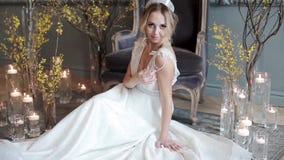 Novia rubia en el vestido de boda blanco de la moda con maquillaje almacen de video