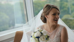 Novia rubia feliz con un ramo de la boda que se sienta en el café en la tabla metrajes
