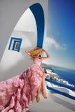 Novia rubia hermosa del fugitivo en el vestido de boda blanco fabuloso con un tren muy largo de cristales en la calle en Santorin foto de archivo