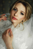 Novia rubia hermosa en maquillaje y velo en los clos blancos de un vestido Foto de archivo