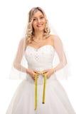 Novia rubia que mide su cintura Imagen de archivo libre de regalías
