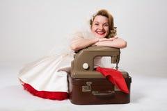 Novia sonriente con la sentada retra de la máquina de coser fotos de archivo libres de regalías