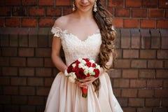 Novia sonriente en el vestido que se casa blanco con un ramo de rosas rojas y blancas imagen de archivo