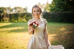 Novia sonriente en un vestido que se casa blanco que sostiene un ramo beauriful de las rosas rojas imagenes de archivo