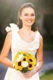 Novia sonriente fresca elegante en un vestido blanco con un ramo de s foto de archivo
