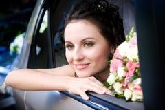 Novia sonriente que se sienta en el coche fotografía de archivo