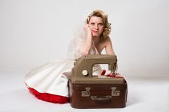 Novia triste con la máquina de coser retra que se sienta en estudio fotografía de archivo libre de regalías