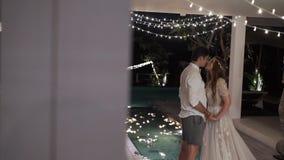 Novia y abrazo y beso del novio en un chalet tropical en la noche Luces en fondo almacen de video