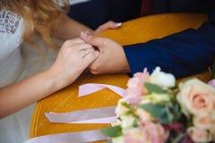 Novia y groom& x27; manos de s con los anillos de bodas en la tabla marrón Imagen de archivo libre de regalías