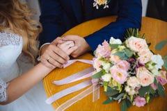 Novia y groom& x27; manos de s con los anillos de bodas en la tabla marrón Foto de archivo