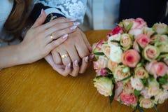 Novia y groom& x27; manos de s con los anillos de bodas en la tabla marrón Imagenes de archivo