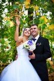 Novia y novio alegres en hojas de otoño Imagen de archivo