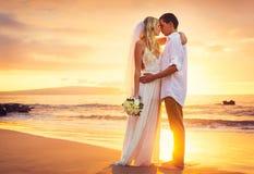 Novia y novio, besándose en la puesta del sol en una playa tropical hermosa