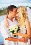 Novia y novio, besándose en la puesta del sol en una playa tropical hermosa Imagen de archivo libre de regalías