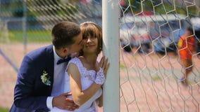 Novia y novio cerca de la puerta del fútbol que tiene tiempo de la diversión metrajes