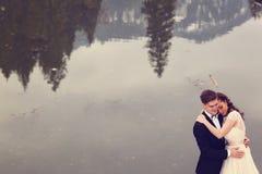 Novia y novio cerca del lago Imagen de archivo libre de regalías
