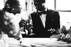 Novia y novio Clinking Glasses Together de la ascendencia africana imagen de archivo