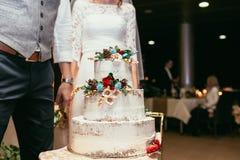 Novia y novio con el pastel de bodas rústico en banquete de la boda con Imagen de archivo libre de regalías