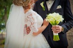Novia y novio con el ramo de la boda ciérrese encima de fondo Imagen de archivo