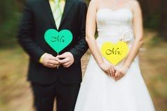 Novia y novio con las tarjetas en la forma del corazón Fotos de archivo